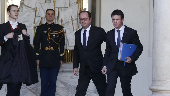 French Prime Minister Manuel Valls talks to French President Francois Hollande leave the Elysee Palace following the weekly cabinet meeting in Paris