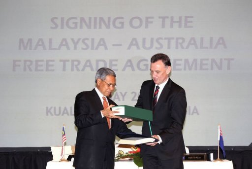Malaysia Trade Minister Mustapha Mohamed (L) exchanges documents with Australia Trade Minister Craig Emerson