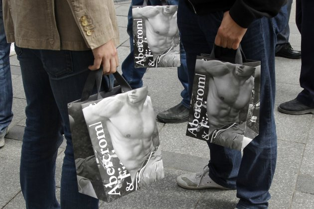 Shoppers hold bags with purchases on the opening day of operations by retailers Abercrombie & Fitch outside their Paris store