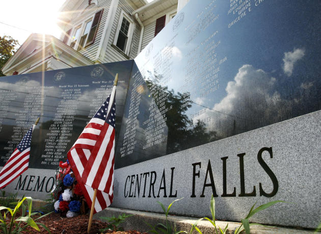 In this July 7, 2011 photo, flags are planted at a veterans memorial in Central Falls, R.I. Rhode Island's most distressed city is on the cusp of declaring bankruptcy _ a relatively rare step for muni