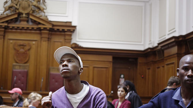 """Xolile Mngeni, left, shows his family members a thumbs up after being sentenced in court at Cape Town, South Africa, Wednesday, Dec. 5,  2012. A South African judge sentenced the triggerman in the 2010 honeymoon slaying of a Swedish bride to life in prison Wednesday, calling the shooter """"a merciless and evil person"""" who deserved the maximum punishment for his crime. Prosecutors say the newlywed's British husband orchestrated the November 2010 killing. Judge Robert Henney did not hold back his contempt while sentencing Xolile Mngeni for the killing of 28-year-old Anni Dewani. Henney said that the shooter showed no remorse. (AP Photo/Schalk van Zuydam)"""