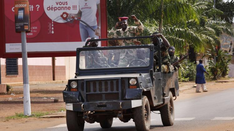 A Seleka soldier raises his fist while riding in a jeep during fighting in Bangui