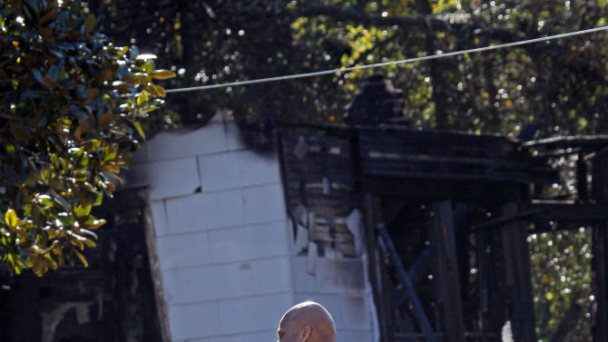 An officer with the Jackson, Miss., Fire Department takes a call Wednesday, Nov. 14, 2012, while observing the burned out house where authorities say a small plane carrying three people crashed shortly after 5 p.m. Tuesday evening. The home's resident escaped with non-life threatening injuries but all three pilots aboard were killed, authorities said. (AP Photo/Rogelio V. Solis)