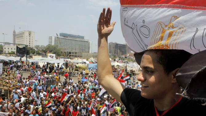 An Egyptian protester covers his head by a national flag during a demonstration against Egypt's Islamist President Mohammed Morsi in Tahrir Square in Cairo, Monday, July 1, 2013. Elsewhere in Cairo, protesters stormed and ransacked the headquarters of President Mohammed Morsi's Muslim Brotherhood group early Monday, in an attack that could spark more violence as demonstrators gear up for a second day of mass rallies aimed at forcing the Islamist leader from power. (AP Photo/Amr Nabil)