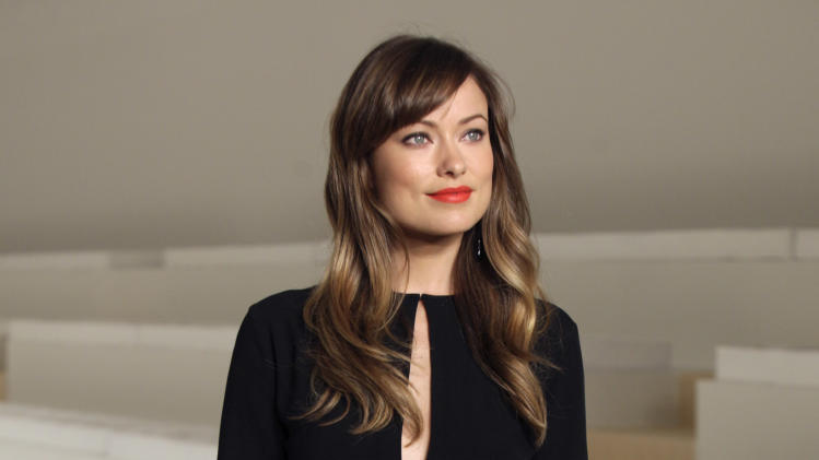 Actress Olivia Wilde poses for photos before the spring 2012 Ralph Lauren Collection is modeled during Fashion Week in New York, Thursday, Sept. 15, 2011. (AP Photo/Richard Drew)