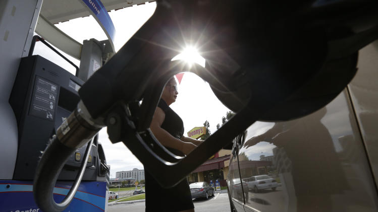 Lorena Delara fills up her tank with gasoline at a gas station Friday, Oct. 5, 2012, in San Diego. A 20-cent jump overnight in California gas prices has put the state ahead of Hawaii for the nation's most expensive gas. (AP Photo/Gregory Bull)