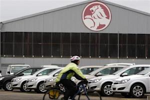 A cyclist rides past a General Motors Holden storage facility in Melbourne