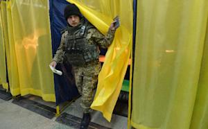 A Ukrainian serviceman exits a booth in a polling station…