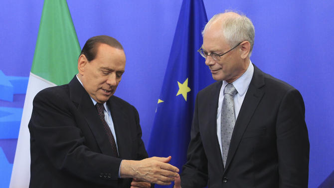 Italy's Prime Minister Silvio Berlusconi, left, shows his injured right hand to European Council President Herman Van Rompuy, prior to a meeting, at the European Council building in Brussels, Tuesday, Sept. 13, 2011. (AP Photo/Yves Logghe)