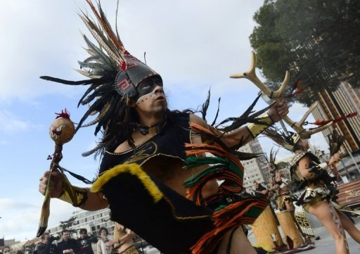 <p>Dancers in costumes and head-dresses perform in Madrid in a ceremony marking the end of the Mayan age on December 21, 2012. A global day of lighthearted doom-themed celebration and superstitious scare-mongering culminated Friday in the jungle temples built by the Mayan people of Central America, whose calendar sparks fears of apocalypse.</p>