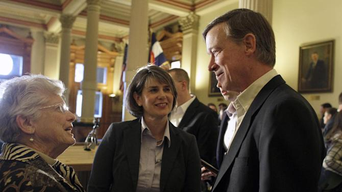 "This photo taken Jan. 3, 2013 shows Colorado Gov. John Hickenlooper, right, with Sue Birch, Executive Director of the Colorado Department of Health Care Policy and Financing, center, speaking with an attendee of a news conference where Hickenlooper announced a plan to expand Medicaid coverage for adults as called for by President Barack Obama's federal health care law, at the state Capitol in Denver. The underdog of government health care programs is emerging as the rare early success story of President Barack Obama's technologically challenged health overhaul. A yearslong effort to reach eligible residents apparently succeeded in generating the increased demand. The state has installed self-service kiosks in community clinics, hospitals and libraries to sign people up. And a year ago, nurses statewide agreed to help by promoting Medicaid to low-income uninsured patients. ""We said to our nurses: 'OK, you're our bounty hunters. You go find our patients,'"" Birch said. (AP Photo/Brennan Linsley)"