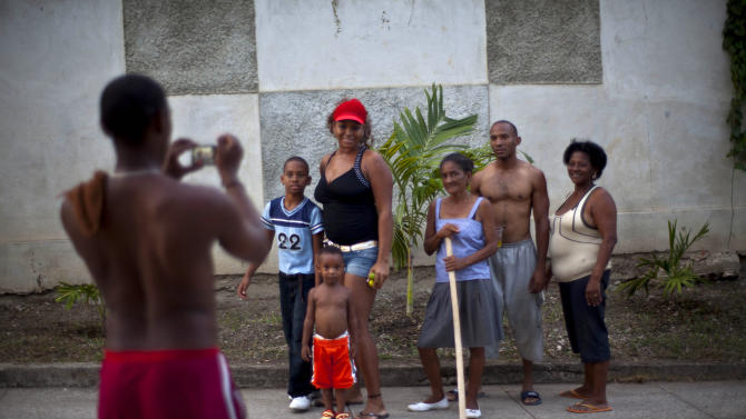 Cubans pose for a picture on a sidewalk in Guantanamo, Cuba, on the eve of the country's Revolution Day, Wednesday, July 25, 2012. Revolution Day marks the July 26, 1953 rebel attack led by Fidel and Raul Castro on the Moncada military barracks. The attack is considered the beginning of the revolution that culminated with dictator Fulgencio Batista's ouster. (AP Photo/Ramon Espinosa)