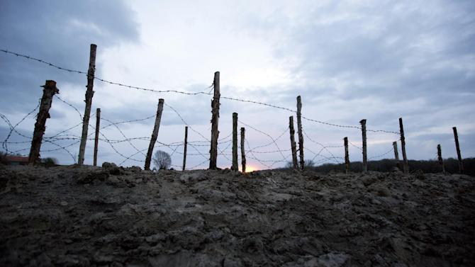 In this photo taken on Saturday, Dec. 20, 2014, the sun begins to rise in back of barbed wire next to a re-constructed WWI trench in Ploegsteert, Belgium. Chlorine gas - sent crawling in favorable winds over Flanders Fields from German positions - sowed terror and agony for the first time on April 22, 1915. The era of chemical weaponry had dawned. The weapon of mass slaughter came to symbolize the ruthlessness and, many say, futility of the 1914-1918 Great War. (AP Photo/Virginia Mayo)