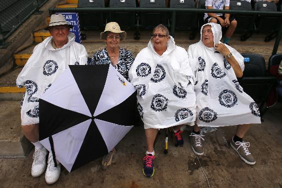 CORRECTS DATE AND YEAR TO AUG. 20, 2014 - Little League baseball fans sit in the rain waiting for the beginning of a delayed semifinal International baseball game between Tokyo and Seoul at the Little League World Series tournament in South Williamsport, Pa., Wednesday, Aug. 20, 2014