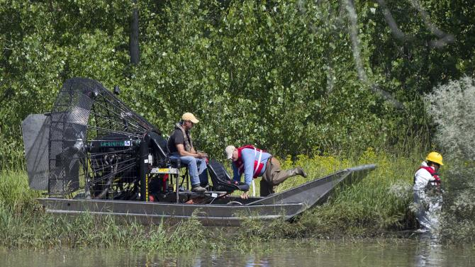 Oil spill cleanup crew workers disembark from an air boat to begin work on a flooded plain bordering the Yellowstone River, Monday, July 11, 2011, near Laurel, Mont. Exxon Mobil Corp. employees use an air boat to scan an area along the flood plain of the Yellowstone River, Monday, July 11, 2011, near Laurel, Mont. Because of the high river levels, cleanup and testing efforts of a 42,000 gallon oil spill into the River on July 1 have been difficult. Air boats have been able to scan slow moving water ways but have not been able to launch jet boats into the channel yet. (AP Photo/Julie Jacobson)