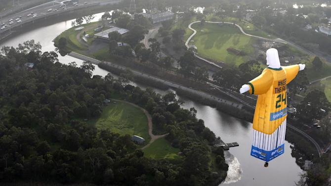 In this photo provided sportsbet.com.au, a hot air balloon in the likeness of Brazil's Christ The Redeemer statute, wearing the colors of Australia's soccer team floats over the Melbourne skyline Tuesday, June 10, 2014. Australia will begin their 2014 soccer World Cup campaign with a match against Chile Saturday, in Cuiaba