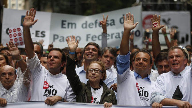 Rio de Janeiro's Governor Sergio Cabral, second from right, Brazilian actress Fernanda Montenegro, center, and Rio de Janeiro's Mayor Eduardo Paes, second from left, lead a march in Rio de Janeiro, Brazil,  Monday, Nov. 26, 2012. Thousands of demonstrators gathered in downtown Rio de Janeiro for a march against legislation that officials here insist would strip this oil-producing state of much of its income from the energy sector. (AP Photo/Victor R. Caivano)
