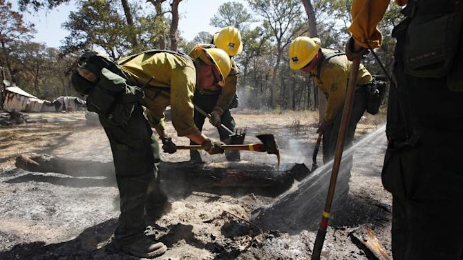 A fire fighting crew from the Lassen National Forest in Calif., clean up hot spots after the destructive wildfire in Bastrop, Texas, Sept. 10, 2011.  Officials in Texas say fire crews are making progress fighting a massive Texas wildfire but concerns about hotspots are keeping thousands of residents in the Bastrop area from returning home.  (AP Photo/Eric Schlegel - POOL)