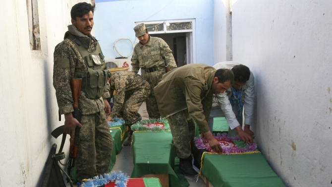 Afghan Army soldiers prepare the coffins for their killed comrades in the morgue of the main hospital in Ghazni, Afghanistan, Wednesday, April 17, 2013. A roadside bomb killed the five soldiers who were part of a government security force guarding a convoy of trucks in Ghazni's Qarabagh district. Roadside bombs and insurgent attacks killed dozens of people in five separate attacks across Afghanistan as violence steadily rises during this year's spring fighting season, officials said Wednesday.  (AP Photo/Rahmatullah Nikzad)