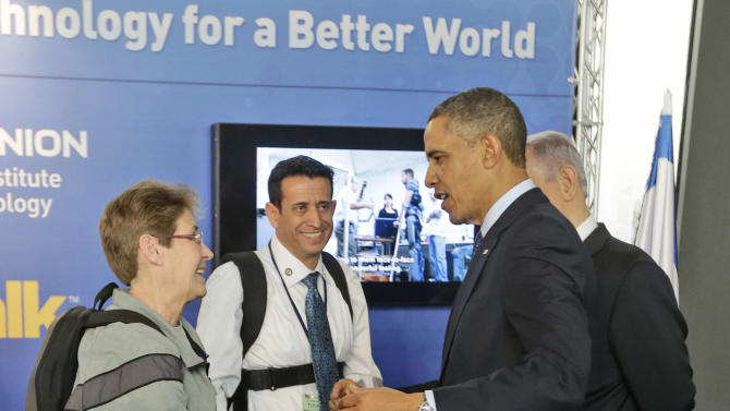 U.S. President Barack Obama and Israeli Prime Minister Benjamin Netanyahu, right in background, talk with Sgt. Theresa Hannigan, left, from Long Island, New York and Radi Kaiuf, center, during their tour of the Technology Expo in Jerusalem, Israel, Thursday, March 21, 2013. Hannigan and Kaiuf where demonstrating technology that assist paraplegics to walk again.(AP Photo/Pablo Martinez Monsivais)