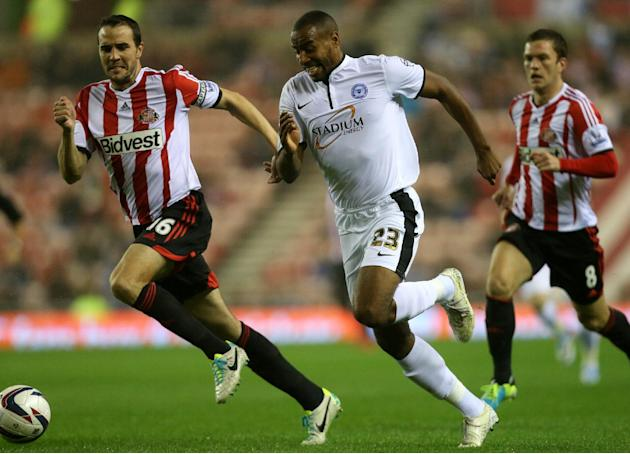 Peterborough's Tyrone Barnet, right, vies for the ball with Sunderland's captain John O'Shea during their English League Cup soccer match at the Stadium of Light, Sunderland, England, Tuesday, Sept. 2