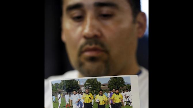 FILE - In this Thursday, May 2, 2013 file photo, Jose Lopez points to an undated photo of Riccardo Portillo, center, his brother-in-law, following a news conference , at Intermountain Medical Center, in Murray, Utah. Portillo, a 46-year-old soccer referee who was punched by a teenage player during a game and later slipped into a coma died Saturday night, May 4, 2013, police said. (AP Photo/Rick Bowmer, File)
