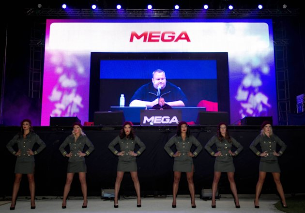 Indicted Megaupload founder Kim Dotcom appears on a large screen during the launch of a new file-sharing website called &quot;Mega&quot; at his Coatesville mansion in Auckland, New Zealand, Sunday, Jan. 20, 2013. The colorful entrepreneur unveiled the site ahead of a lavish gala and press conference on the anniversary of his arrest on racketeering charges related to his now-shuttered Megaupload file-sharing site. (AP Photo/New Zealand Herald, Richard Robinson) New Zealand Out, Australia Out