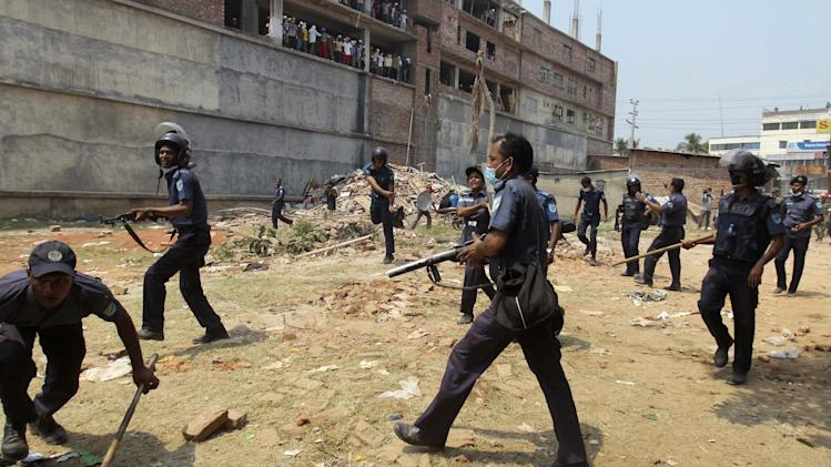 Bangladeshi police officers drive back a crowd at the site of a building that collapsed Wednesday in Savar, near Dhaka, Bangladesh, Friday, April 26, 2013. Clashes erupted after police cordoned off the building site, pushing back thousands of bystanders and relatives, after rescue workers said the crowds were hampering their work. The death toll topped 300 on Friday and it remained unclear what the final grim number would be. (AP Photo/A.M. Ahad)