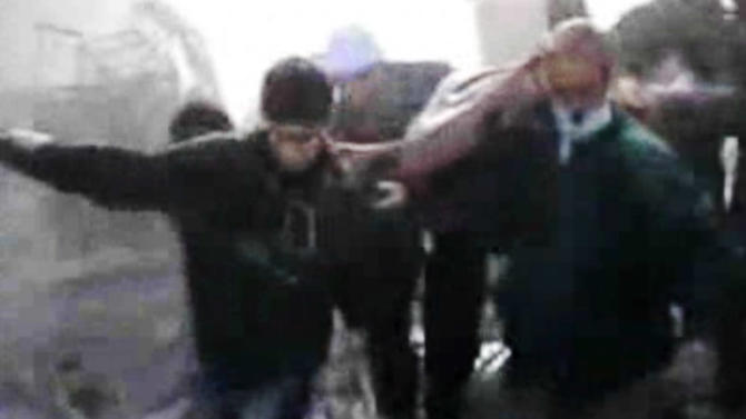 In this image taken from video obtained from Bambuser, which has been authenticated based on its contents and other AP reporting, Syrians help an inured man after an airstrike hit Douma City, Syria on Thursday, Jan. 3, 2013. Airstrikes continued across Syria on Thursday as Syrian President Bashar Assad's military stepped up its assault on areas that surround the nation's capital. (AP Photo/Bambuser via AP video)