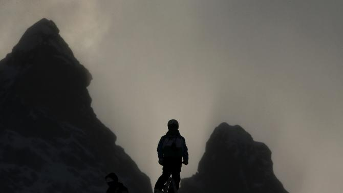 An unidentified coach is silhouetted as he follows the women's World Cup Downhill skiing race in Val d'Isere