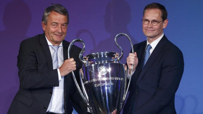 Niersbach, president of the German Football Association (DFB), and Berlin's Mayor Mueller hold the soccer Champions League trophy during the official handover ceremony in Berlin