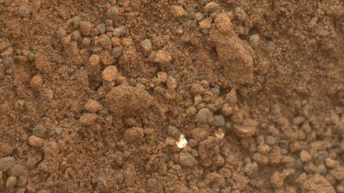 """This handout photo provided by NASA/JPL-Caltech/MSSS, taken Oct. 15, 2012, shows part of the small pit or bite created when NASA's Mars rover Curiosity collected its second scoop of Martian soil at a sandy patch called """"Rocknest."""" The bright particle near the center of this image, and similar ones elsewhere in the pit, prompted concern because a small, light-toned shred of debris from the spacecraft had been observed previously nearby. However, the mission's science team assessed the bright particles in this scooped pit to be native Martian material rather than spacecraft debris.  (APPhoto/NASA/JPL-Caltech/MSSS)"""