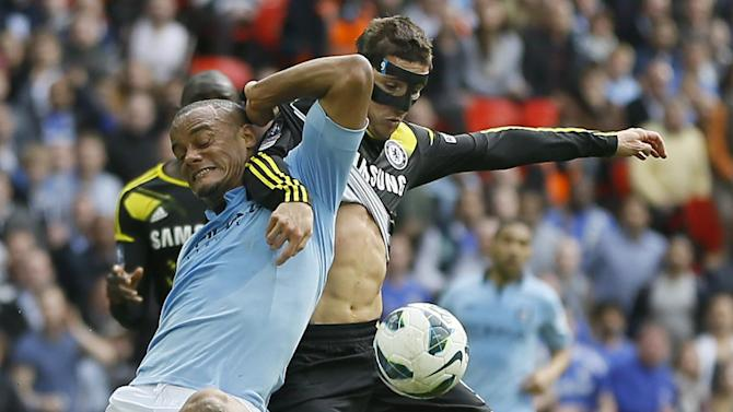 Chelsea's Fernando Torres, right, struggles for the ball with Manchester City's Vincent Kompan, left, during their English FA Cup semifinal soccer match, at Wembley stadium in London, Sunday, April 14, 2013. (AP Photo/Kirsty Wigglesworth)