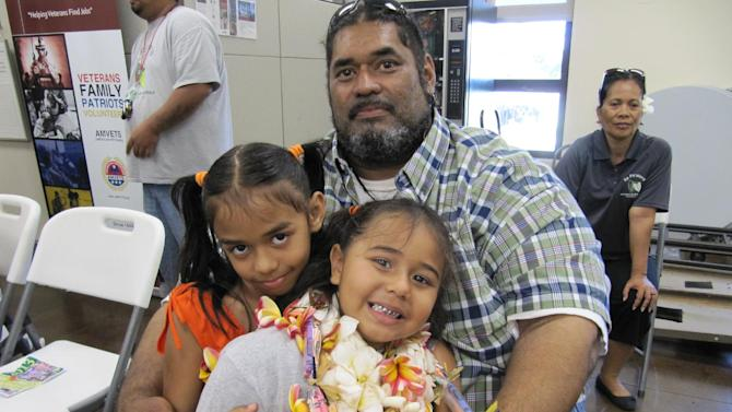 Five-year-old Leomomi Dew, front center, poses for a portrait with her sister Leolani Dew and her father, Leo Dew, after a graduation ceremony for Ka Paalana Traveling Preschool in Honolulu on Thursday, June 27, 2013. (AP Photo/Jennifer Sinco Kelleher)