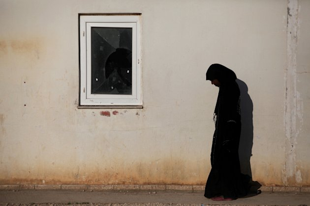 In this Wednesday, March 7, 2012 photo, a displaced Libyan Tawargha woman is seen in a refugee camp in the outskirts of Benghazi, Libya. On the country's Mediterranean coast, Misrata, Libya's third largest city and its business center, local militiamen expelled some 40,000 ethnic Tawargha Africans for allegedly collaborating in the killing and rape of Misratans and for helping Gadhafi's forces in imposing a tight siege on the city during the uprising. (AP Photo/Manu Brabo)
