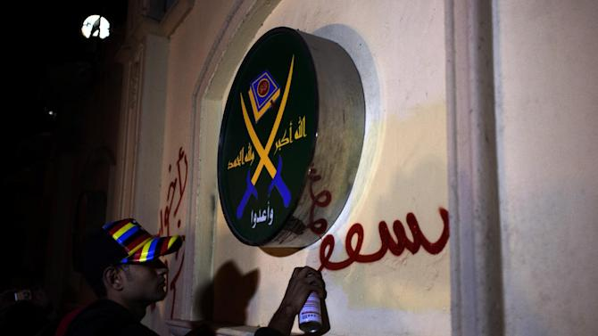 """FILE -- In this Sunday, March 17, 2013 file photo an Egyptian activist spray paints a slogan in Arabic that reads """"Brotherhood are sheep,"""" next to a logo of the Muslim Brotherhood that reads in Arabic """"God is great, thank God, prepare,"""" on the walls of the Brotherhood's headquarters during an anti Muslim Brotherhood protest, in Cairo, Egypt. Egyptians are closely following protests in Turkey, a country that has provided the heavily polarized and increasingly impoverished Egyptians with a tantalizing model for marrying Islamist government with a secular establishment and achieving prosperity along the way. Outside the Muslim Brotherhood, most Egyptians have been skeptical about the Brotherhood's analogy with the Turkish model and view it as a tactic to market itself in the West and assuage fears at home of strict Islamic rule. (AP Photo/Nasser Nasser, File)"""