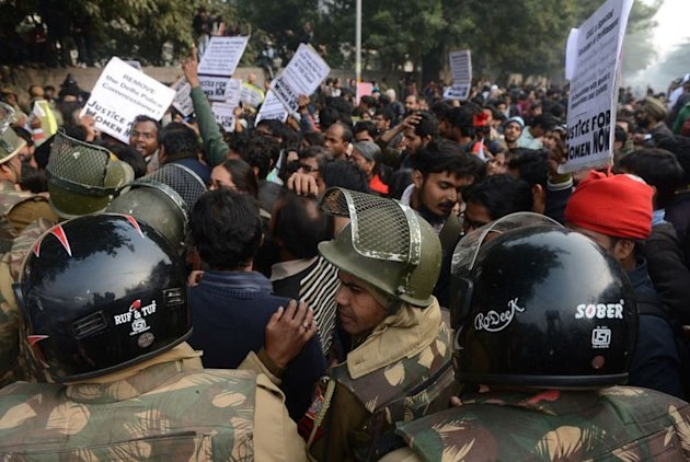 Indian riot policemen stand in front of a demonstrating crowd during a protest calling for better safety for women in New Delhi on December 27, 2012. A 17-year-old Indian girl who was gang-raped committed suicide after police pressured her to drop the case. Amid the uproar over the gang-rape of a student in New Delhi earlier this month, the latest case has again shone the spotlight on police