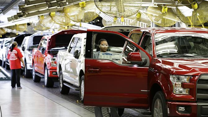 In this March 13, 2015 photo, workers inspect new 2015 aluminum-alloy body Ford F-150 trucks at the company's Kansas City Assembly Plant in Claycomo, Mo. Ford reports quarterly financial results on Tuesday, July 28, 2015. (AP Photo/Charlie Riedel)