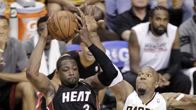 Miami Heat guard Dwyane Wade (3) passes off as he is stopped by Indiana Pacers forward David West (21) and guard Paul George (24) during the first half of Game 6 of their NBA basketball Eastern Conference semifinal playoff series in Indianapolis, Thursday, May 24, 2012. (AP Photo/Michael Conroy)