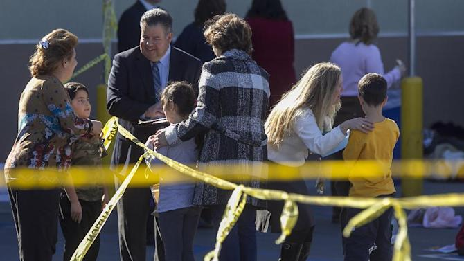 School administrators reunite elementary school children with their parents after their school was evacuated for a bomb threat in Glendale, Calif., Monday, Jan. 7, 2013.  The bomb threat prompted the evacuation of hundreds of children from R.D. White Elementary School on Monday while police searched buildings to make sure the campus was safe. An anonymous caller phoned the school at around 8:30 a.m., and said there was a bomb at the campus, according to police Sgt. Tom Lorenz. (AP Photo/Damian Dovarganes)