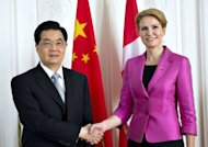 Denmark's Prime Minister Helle Thorning-Schmidt (R) shakes hands with Chinese President Hu Jintao before their meeting at the Prime Minister's office at the Danish Parliament building in Copenhagen. Hu signed deals worth billions of euros with Denmark Saturday and got words of encouragement on his country's bid to expand its influence in the oil-rich Arctic