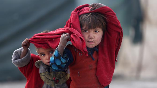 In this Wednesday, Dec. 24, 2014 photo, internally displaced Afghan girls are seen at a camp in Kabul, Afghanistan. Thousands of Afghans are pouring into makeshift camps in the capital where they face a harsh winter as the Taliban return to areas once cleared by foreign forces, who this week are marking the end of their combat mission. (AP Photo/Massoud Hossaini)