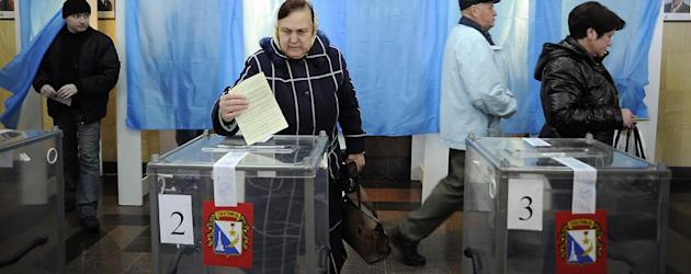 A woman casts her ballot at a polling station during the Crimean referendum. (Andrew Lubimov/AP) (