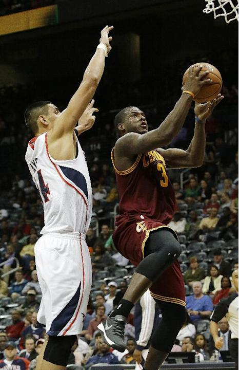 Cleveland Cavaliers shooting guard Dion Waiters (3) goes up for a basket as Atlanta Hawks forward Gustavo Ayon defends  in the second half of an NBA basketball game Friday, Dec. 6, 2013, in Atlanta