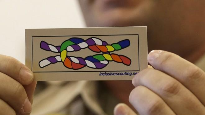 Former scout master Mark Noel holds up a new merit badge of inclusion at a press conference one day before the BSA announced its new policy.
