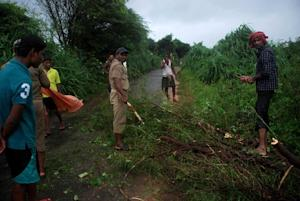 Indian policemen and volunteers clear branches after …