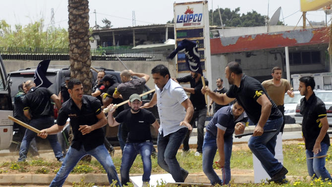 Hezbollah supporters clash with supporters of the Lebanese Option Party during a protest in front of the Iranian Embassy in Beirut, Lebanon, Sunday, June 9, 2013. A senior Lebanese military official says clashes have erupted outside the Iranian embassy in the capital between protesters opposing Hezbollah's participation in the Syrian war and unidentified Lebanese, killing one demonstrator. (AP Photo)