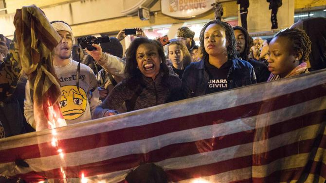 """Demonstrators burn an American flag during a """"Justice for Mike Brown"""" march and rally in Washington"""