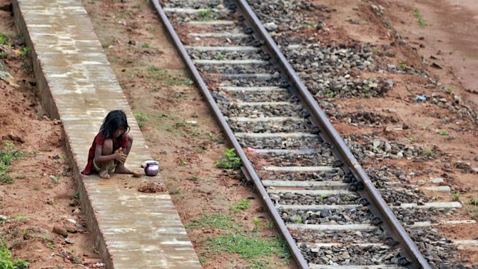 A girl plays with clay next to a railway track on a hot summer day in Agartala