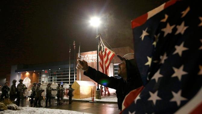 A protester shouts at the National Guard standing on duty outside the Ferguson Police Department after the grand jury verdict in the Michael Brown shooting in Ferguson, Missouri